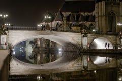 反射在镇运河的中世纪石桥梁在晚上 图库摄影
