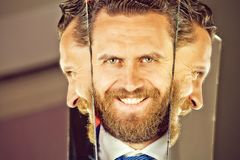 反射在镜子的有胡子的行家人或商人的愉快的面孔 库存图片