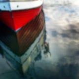 反射在水中的Defocused红色小船 库存图片