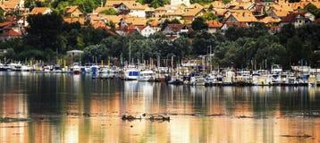 反射在水外面有五颜六色的小船的小游艇船坞 免版税图库摄影