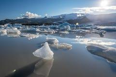 反射在Fjallsarlon面对冰川的湖中水的小冰山对太阳 南冰岛 免版税库存照片