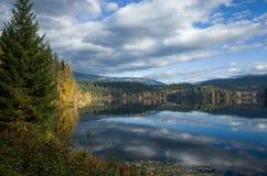 反射多云天空的平静的山湖 免版税库存图片