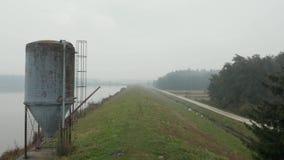 反射性有薄雾的湖在与一个大金属筒仓的一个早期的秋天早晨,空中 影视素材