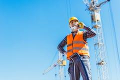 反射性背心和安全帽谈话的微笑的建筑工人 免版税库存照片