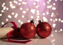 反射性表面上的两个红色圣诞节球 免版税库存图片