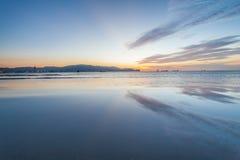 反射日出或日落视图与橙色云彩和蓝天 免版税库存图片