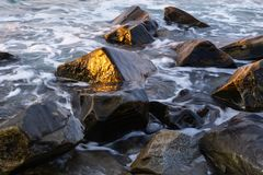 反射湿岩石的阳光在清早 库存图片