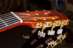 黑反射的表面上的吉他床头柜 免版税库存图片