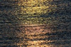 反射风平浪静水的阳光在日出 抽象文本 免版税库存照片