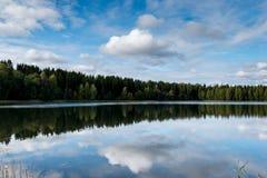 反射9月挪威,森林在有蓝天和棉花糖的一个湖在秋天覆盖 库存图片