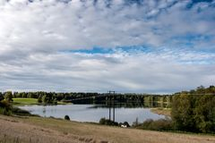 反射9月挪威,森林在有蓝天和棉花糖的一个湖在秋天覆盖 免版税库存照片