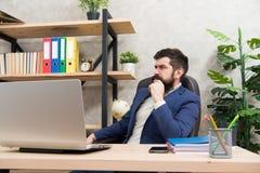反应在企业电子邮件 残酷商人在办公室 有胡子工作的成熟人在膝上型计算机 有胡子的行家用途 图库摄影