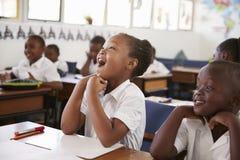 反应在教训期间的女孩在一所小学 库存图片