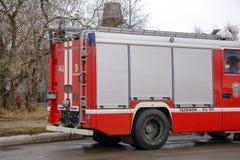 反应紧急状态的消防车驾驶与警报器和蓝色光通过埃克塞特的中心 图库摄影