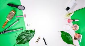 反弹的顶视图夏天情人节3月8日党成套装备布局女性辅助部件化妆用品在绿色白色背景生叶 库存图片