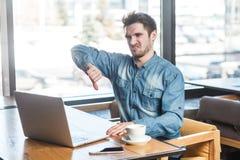 反感!消极蓝色牛仔裤衬衣的批评有胡子的年轻自由职业者侧视图画象在咖啡馆坐并且做录影 免版税库存照片