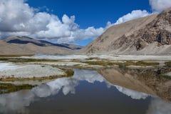 反映一个蓝色泥泞的盐湖的表面有白色盐层数的和一个碗高山,在明亮的天空美丽的白色云彩 库存照片