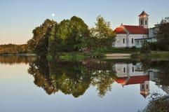 反映在小池塘的树和教会 库存图片
