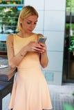 发与她的手机的可爱的少妇正文消息 免版税库存图片