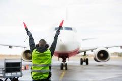 发信号对在跑道的飞机的地勤人员 免版税图库摄影