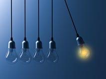 发光一个垂悬的电灯泡不同和从象牛顿摇篮的未点燃的白炽电灯泡引人注意在深蓝背景 免版税库存照片