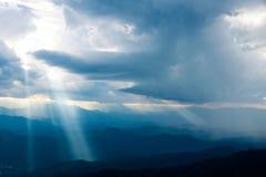 发光下来从天堂的太阳在山 免版税库存照片