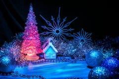 发光与在蓝色背景的桃红色光的冰冷的圣诞树 免版税库存照片