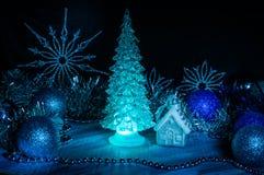 发光与在蓝色背景的蓝色光的冰冷的圣诞树 免版税库存图片