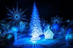 发光与在蓝色背景的蓝色光的冰冷的圣诞树 免版税库存照片