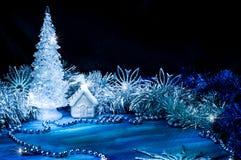 发光与在蓝色背景的银色光的冰冷的圣诞树 库存照片