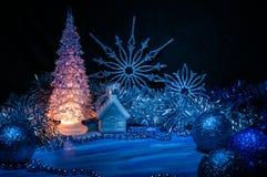 发光与在蓝色背景的黄灯的冰冷的圣诞树 免版税库存照片