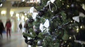 黑发光和表面无光泽的球和白色弓 新年` s和摘要弄脏了与圣诞树的商城背景 影视素材