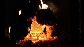 发光在一个热的木熔炉里面的橙色和红色煤炭 免版税库存照片
