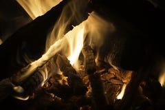 发光在一个舒适营火的火焰和炭烬在晚上 库存图片