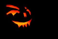 发光在万圣夜黑色背景的南瓜的被雕刻的面孔 免版税库存照片