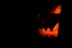 发光在万圣夜黑色背景的南瓜的被雕刻的面孔 图库摄影