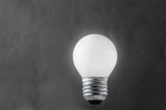 发光在具体背景,想法概念的白光电灯泡 免版税库存照片