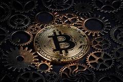 发光在复杂嵌齿轮中间的金黄bitcoin转动特写镜头 隐藏货币概念 免版税库存照片