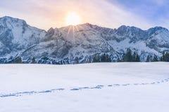 发光在山峰和雪的太阳 免版税库存图片