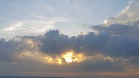 发光在巨大,厚实的黑暗的云彩后的太阳 免版税库存照片