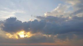 发光在巨大,厚实的黑暗的云彩后的太阳 免版税库存图片