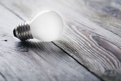 发光在木背景,想法概念的白光电灯泡 库存图片