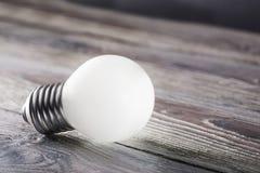 发光在木背景,想法概念的白光电灯泡 免版税库存照片
