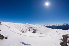 发光在积雪覆盖的山脉和高山峰顶的太阳星在意大利高山弧,在一个明亮的晴天冬天 图库摄影