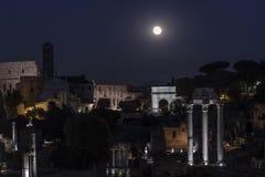 发光在罗马广场和罗马斗兽场上的满月 库存图片