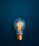 发光在蓝色背景创造性的想法背景的电灯泡 库存照片