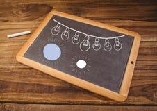 发光在黑板的电灯泡和太阳 免版税图库摄影