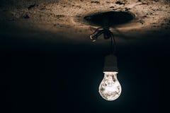 发光在黑暗的地下室的老电灯泡 在建造场所的电即兴创作 库存图片