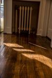 发光横跨与老幅射器加热器的坚实橡木地板的太阳在背景中 库存照片