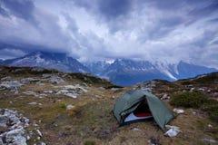 发光由阳光的高山谷 绿色帐篷在牧场地 受欢迎的旅游胜地 与帐篷的剧烈和美丽如画的场面 库存图片